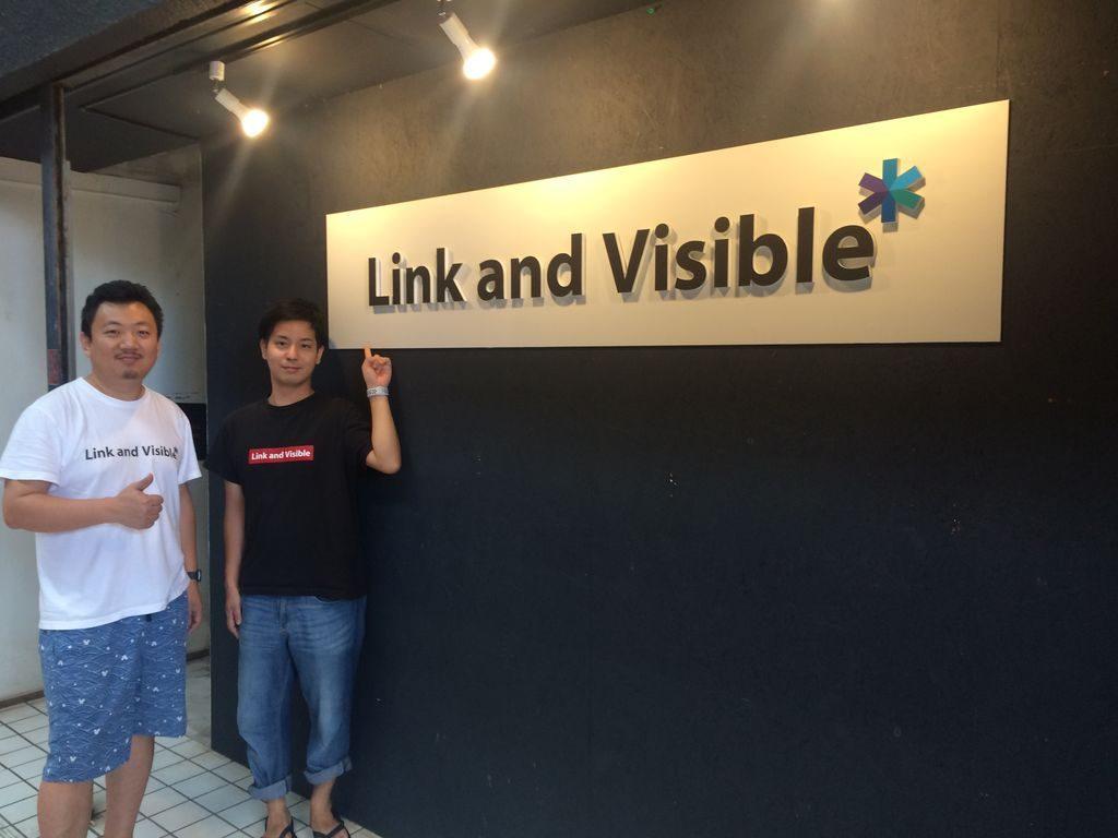 LinkandVisibleの看板と豊里健一郎さんとドゥさん